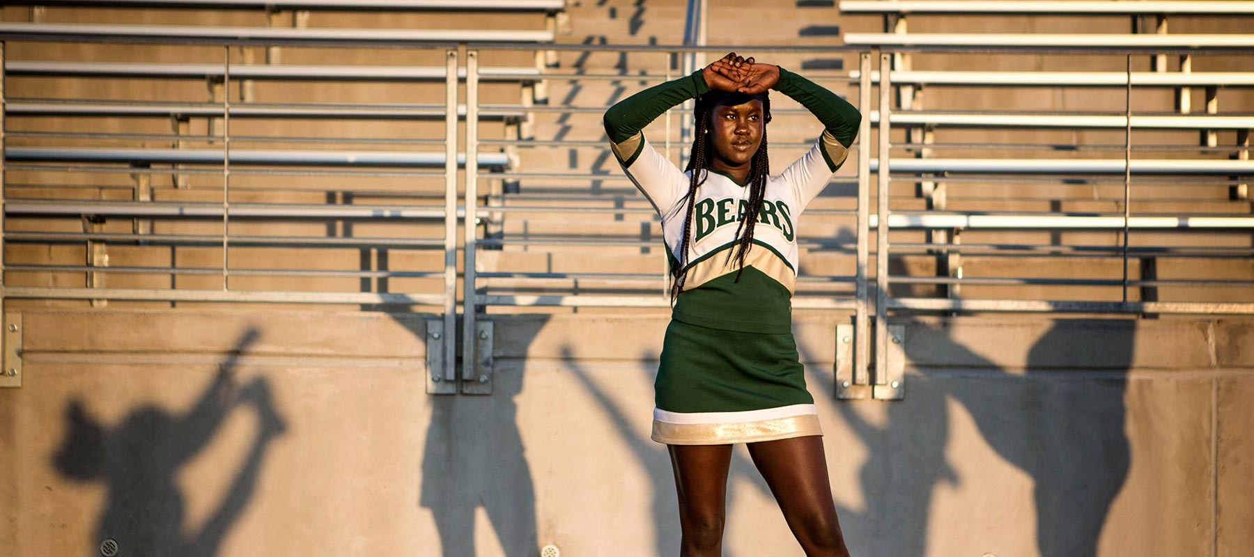 Nyakan Timbek, a senior cheerleader at Omaha Bryan, blocks the sun from her eyes while her team practices kicks.