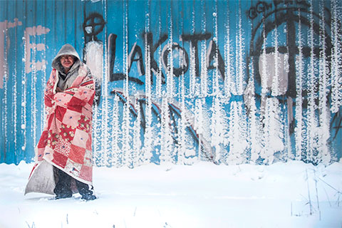 A Lakota Sioux native stands in front of graffiti near the town of Whiteclay