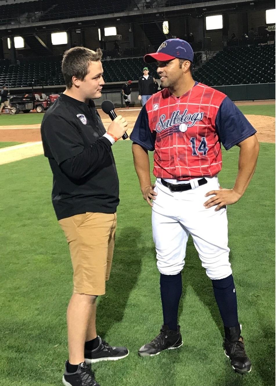 Ryan Schreurs (left) interviews Randolph Oduber, a Salt Dogs baseball player, during Schreurs' internship in summer 2018.