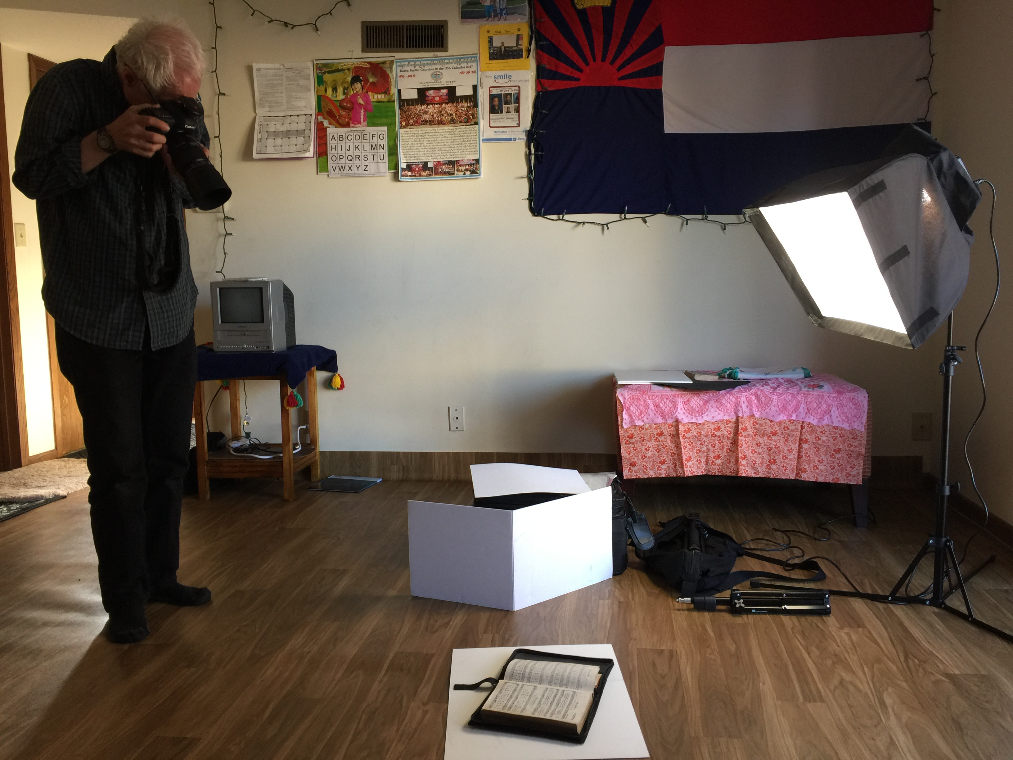 Jim Lommasson photographs a book that a Lincoln Yazidi family brought with them to the United States. As part of an ongoing project, Lommasson documents objects that Iraqi refugees brought to America.  (Photo by Abby Groth)