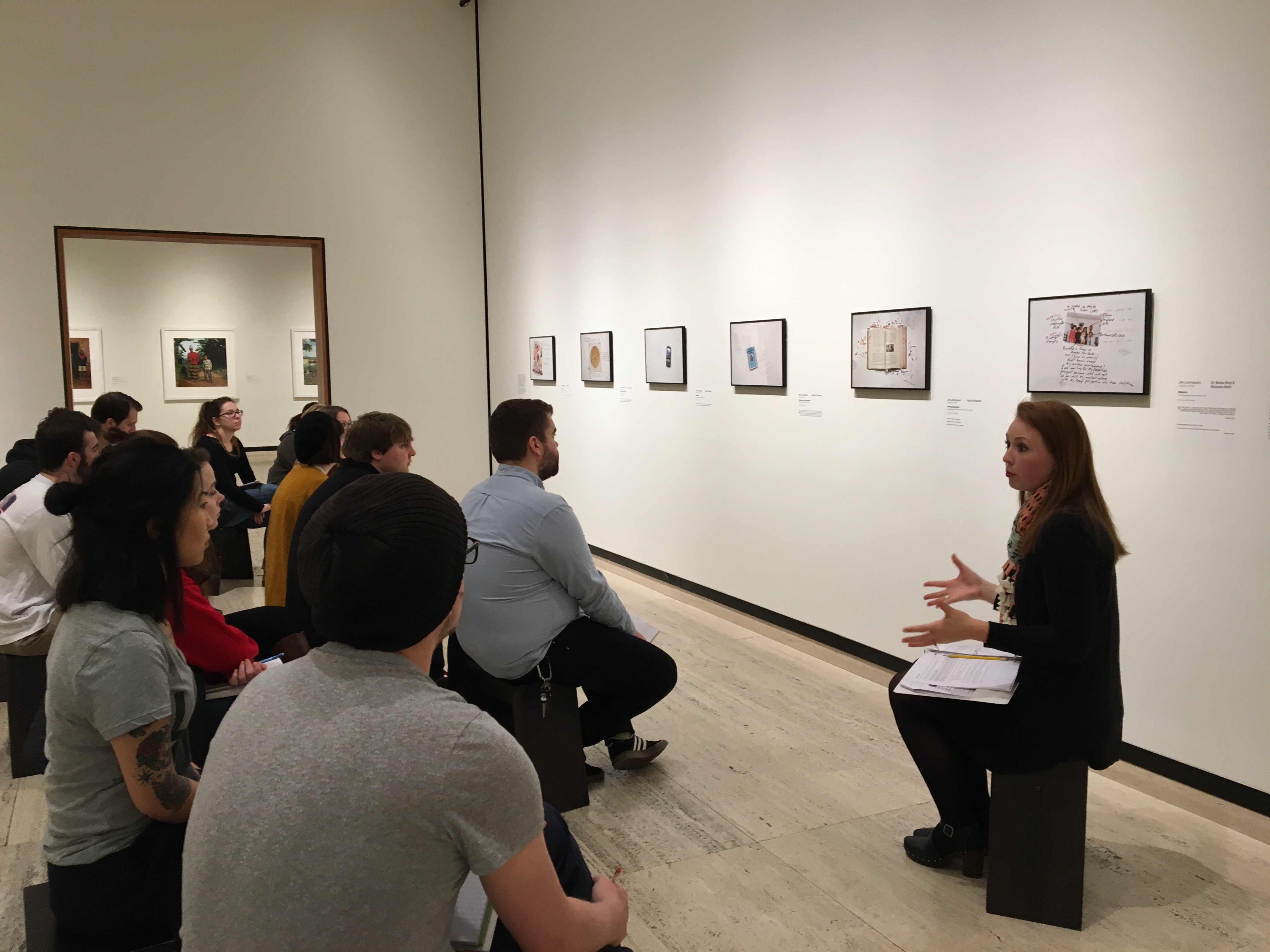 Students in the Nebraska Mosaic class listen as Abby Groth, assistant curator of public programs, (far right) discusses the nuances of Jim Lommasson's exhibit at the Sheldon Art Museum. (Photo by Michelle Hassler)