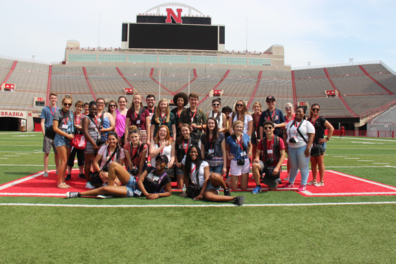 Media Academy students pose at Memorial Stadium with team leaders and professors