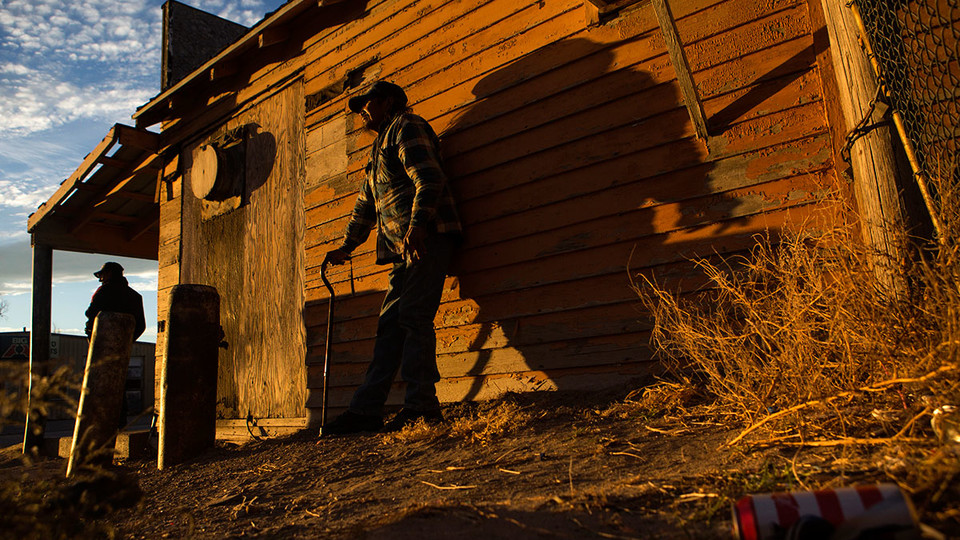 James Wooldridge | Journalism and Mass Communication People stand beside a building as the sun sets over Whiteclay. Many of those who spend time drinking on the streets in Whiteclay spend their nights in a makeshift camp not far from the town.